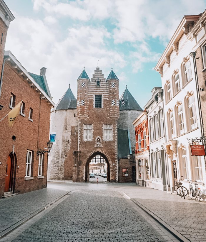 a historic gate in the city bergen op zoom in the netherlands, travel in holland, blue sky with houses