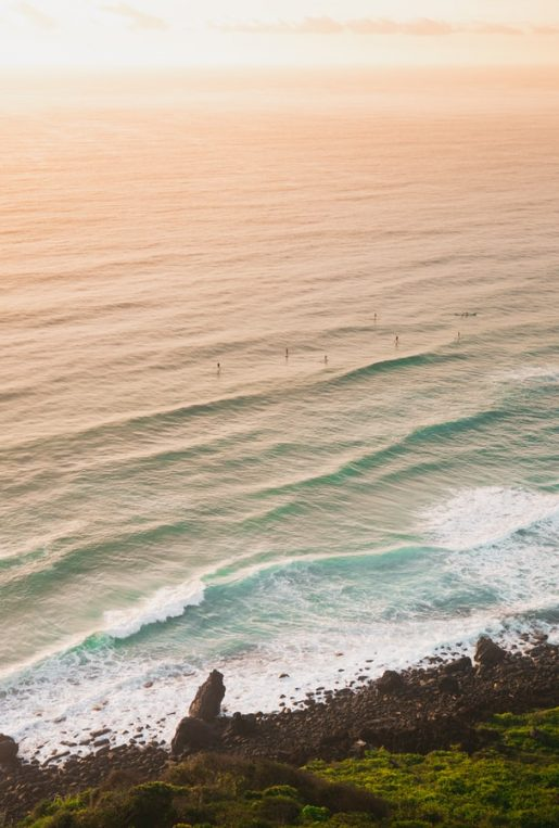 the beach and ocean during sunset with surfers in the water